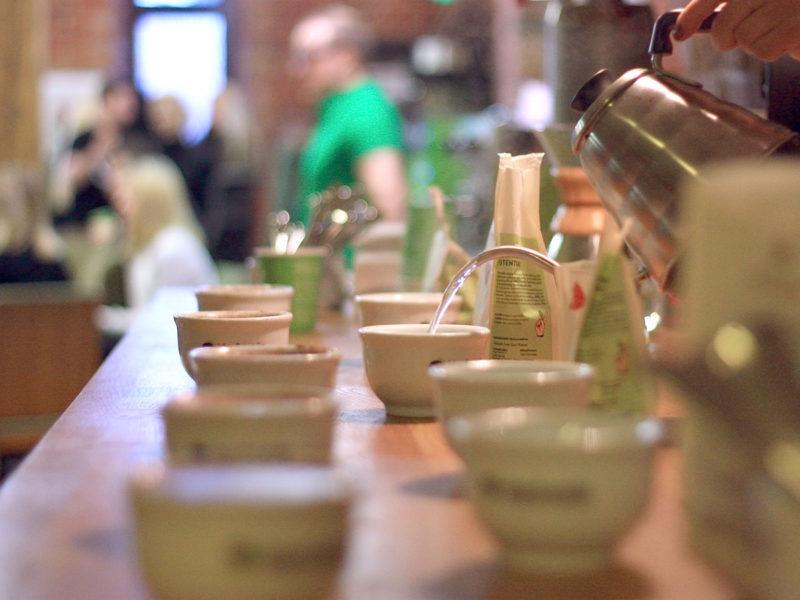 Cup Tastingin valmistelua. Karkeasti jauhettujen kahvien päälle kaadetaan lähes kiehuvaa vettä ja niin kutsuttu blooming-vaihe alkaa.